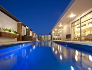Compass Pools Newcastle Lap pool with pool lights on and a water feature